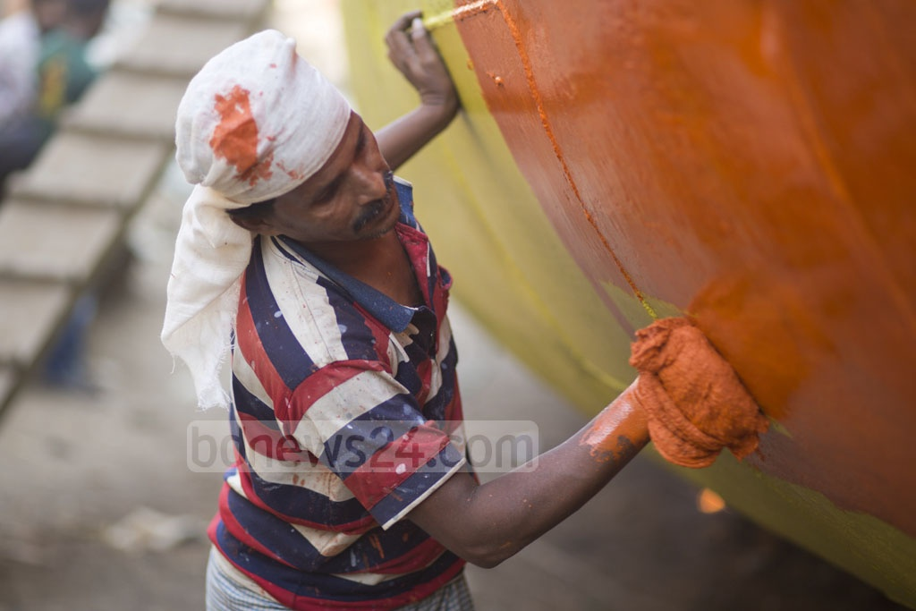 A worker is busy painting a ship in a dockyard at Dhaka's South Keraniganj. Photo: Mostafigur Rahman