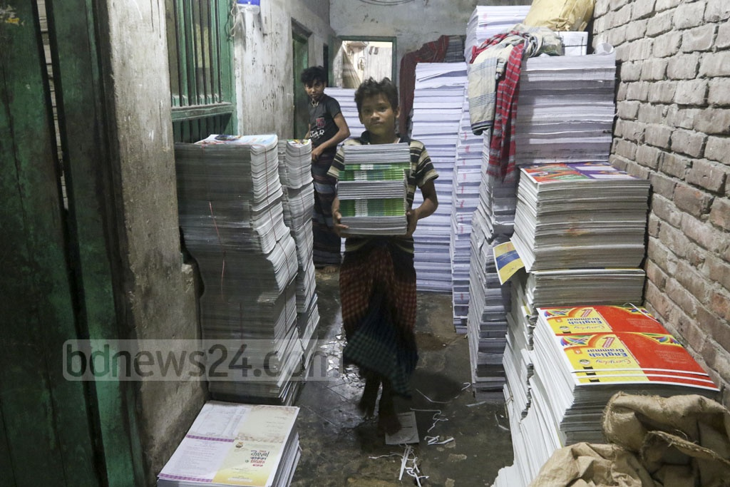 Workers at printing presses are busy these days as the government targets to distribute text books in the beginning of next year. The photo is taken from Dhaka's Sutrapur on Wednesday. Photo: Abdullah Al Momin