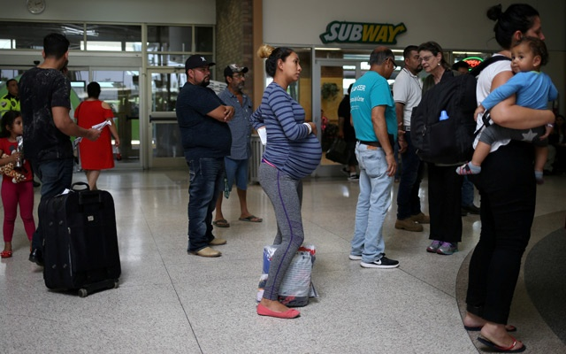 FILE PHOTO: A pregnant woman from Honduras is released from detention with other undocumented immigrants at a bus depot in McAllen, Texas, US, July 28, 2018. Reuters