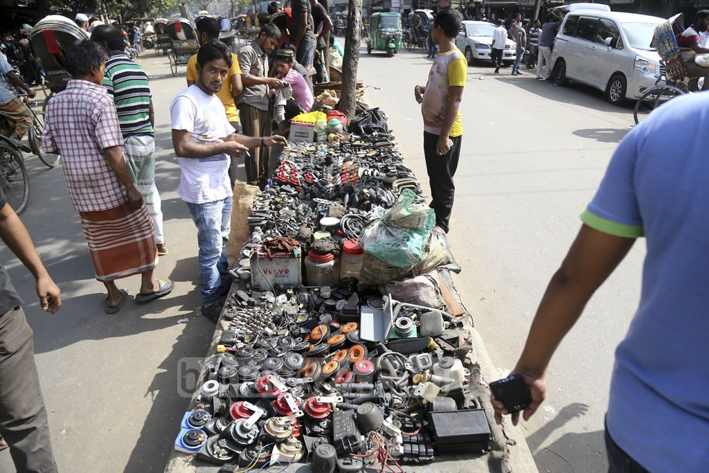 A trader has opened a spare car parts shop on the road divider at Dholaikhal in Old Dhaka. Photo: Mahmud Zaman Ovi