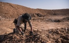 An Iraqi army soldier searches for remains at the mass grave that was discovered at a trash dump site on the outskirts of Hammam Al-Alil after it was liberated by Iraqi forces, in Iraq, Nov 12, 2016. The New York Times