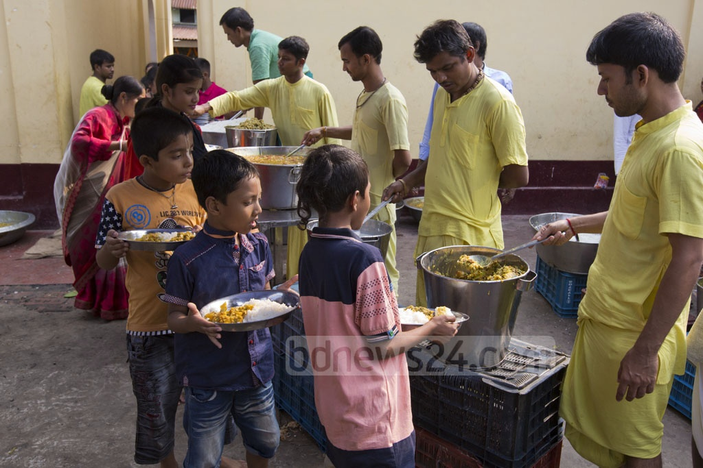 Hindu devotees share food as a ritual during the Annakut festival at the ISKCON Ashram in Dhaka's Swamibagh on Thursday. Photo: Mostafigur Rahman