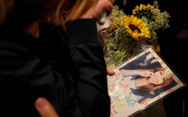 A mourner arrives with a picture of one of her friends at a vigil for the victims of the mass shooting, at the Thousand Oaks Civic Arts Plaza in Thousand Oaks, California, US, Nov 8, 2018. REUTERS/Mike Blake