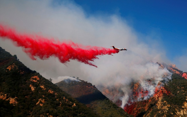 An aircraft drops flame retardant as firefighters battle the Woolsey Fire as it continues to burn in Malibu, California, US, Nov 11, 2018. REUTERS/Eric Thayer