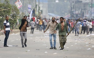BNP workers carrying sticks during clashes with police at Naya Paltan in Dhaka on Wednesday. Photo: Abdullah Al Momin