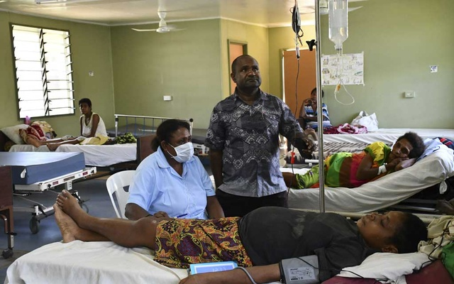 A photo provided by Jo Chandler of Dr Peter Sol, centre, an obstetrician at Kerema Hospital, monitors a patient in the maternity ward in Papua New Guinea. The New York Times