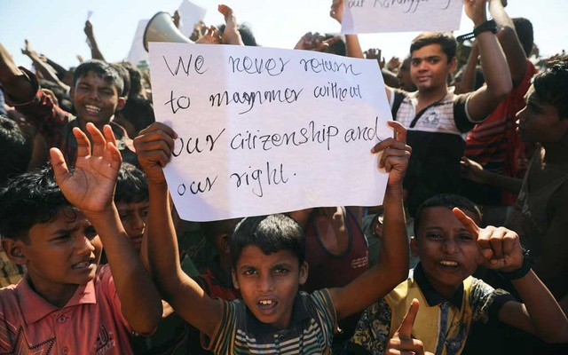 FILE PHOTO:A boy holds a placard as hundreds of Rohingya refugees protest against their repatriation at the Unchiprang camp in Teknaf, Bangladesh November 15, 2018. Reuters