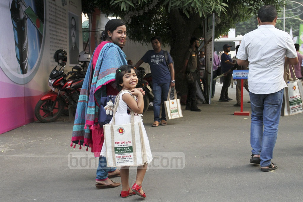 A child and her parents visit the Income Tax Fair at the Officers' Club in Dhaka on Saturday. Photo: Asif Mahmud Ove