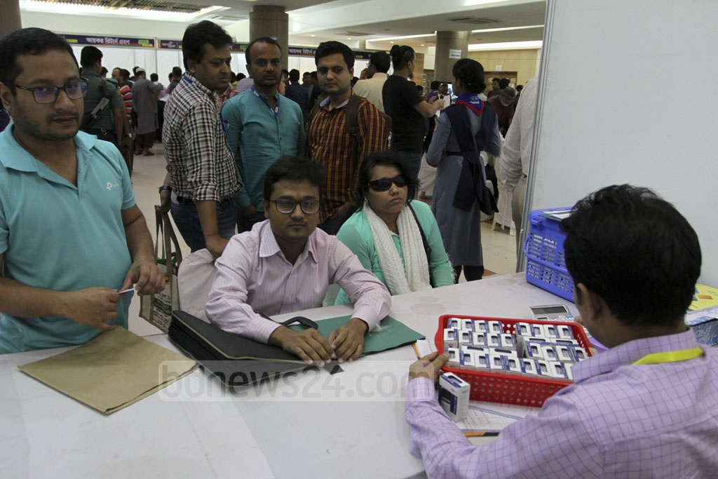 Disabled taxpayers submit their returns at the Income Tax Fair at the Officer's Club in Dhaka on Saturday. A separate booth is installed at the fair this year for the disabled. Photo: Asif Mahmud Ove