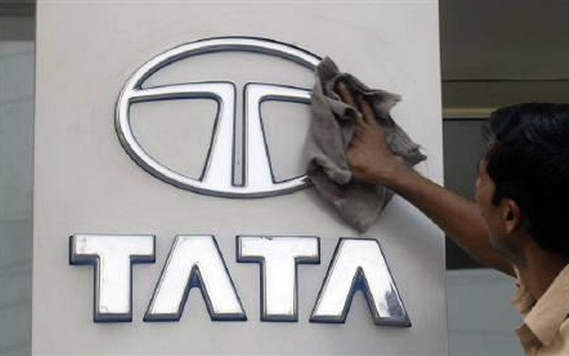 A worker cleans a Tata Motors logo outside its showroom in Hyderabad Oct 26, 2009. REUTERS/Krishnendu Halder/Files