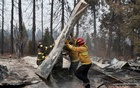 Firefighters move debris while recovering human remains from a trailer home destroyed by the Camp Fire in Paradise, California, US, Nov 17, 2018. REUTERS/Terray Sylvester