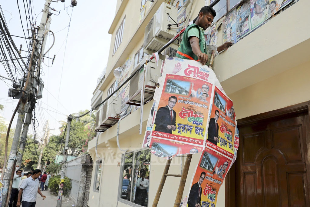 Campaign posters for Awami League nominees are removed from in front of the Awami League's Dhanmondi offices on Monday.