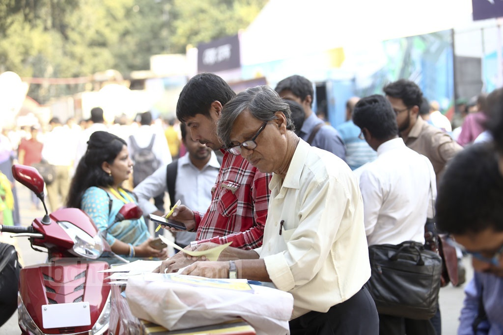 People filling out income tax return forms wherever they can at the crowded National Income Tax Fair 2018 at the Officers' Club on the Bailey Road in Dhaka on the closing day on Monday. Photo: Mahmud Zaman Ovi