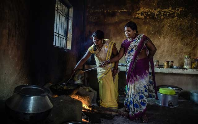 Chain Sahu, right, prepares a meal over a wood fire for election workers at a school in Bhanpuri, India, Nov 12, 2018. Sahu, who has a government-issued smartphone, said she has received calls urging her to vote for the Bharatiya Janata Party, which subsidizes data plans for residents. The New York Times