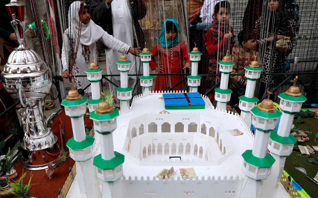 Girls look at a replica of the Grand Mosque of Mecca as they take part in a religious procession to mark Eid-e-Milad-ul-Nabi, the birthday anniversary of Prophet Mohammad, in Rawalpindi, Pakistan November 21, 2018. REUTERS/Faisal Mahmood