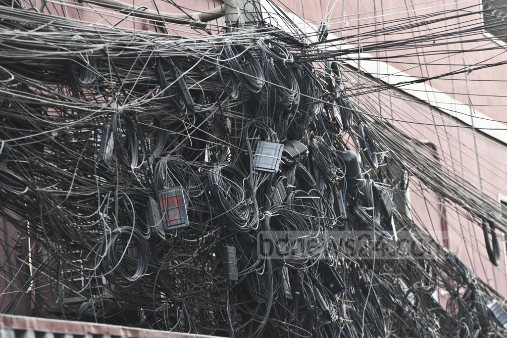 Internet, telephone and cable television service providers continue to entangle the wires for their services with high-voltage power cables, as seen in Dhaka's Fakirapul, despite restrictions on it. Photo: Abdullah Al Momin