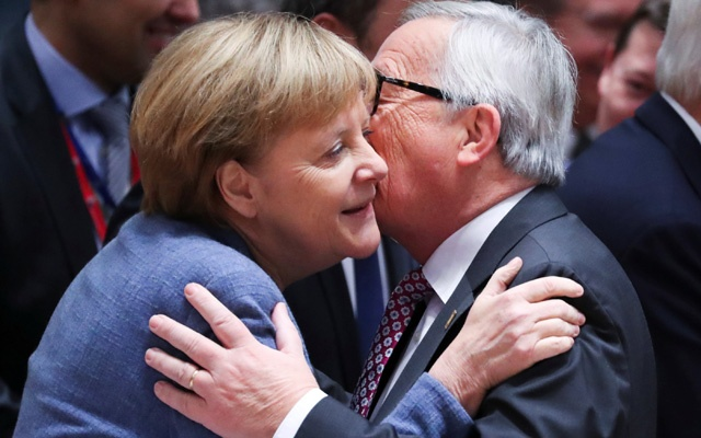 German Chancellor Angela Merkel and European Commission President Jean-Claude Juncker kiss as they take part in an extraordinary EU leaders summit to finalise and formalise the Brexit agreement in Brussels, Belgium Nov 25, 2018. REUTERS/Yves Herman