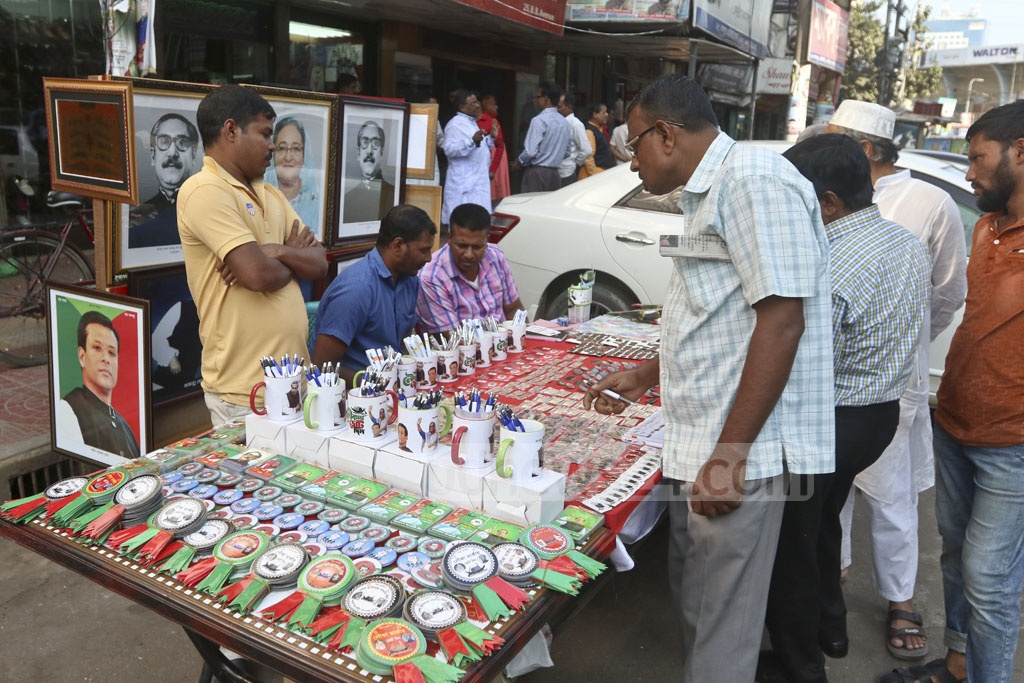 A man is selling campaign materials such as portraits of Bangabandhu Sheikh Mujibur Rahman and Sheikh Hasina, mugs or badges with their photos or lockets of boat logo in front of the Awami League Headquarters on the Bangabandhu Avenue in Dhaka ahead of election. This photo was taken on Wednesday. Photo: Abdullah Al Momin