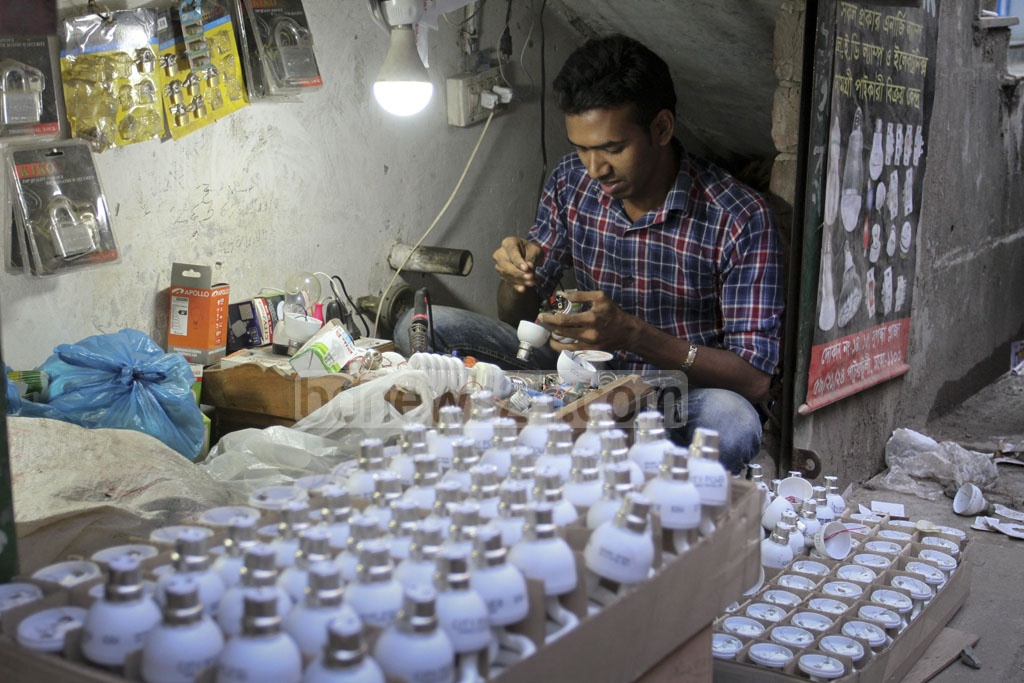 An electrician producing energy-saving bulbs at Patuatuli in Old Dhaka on Thursday. The bulbs made from parts imported from China are sold for Tk 70-120 apiece. Photo: Asif Mahmud Ove