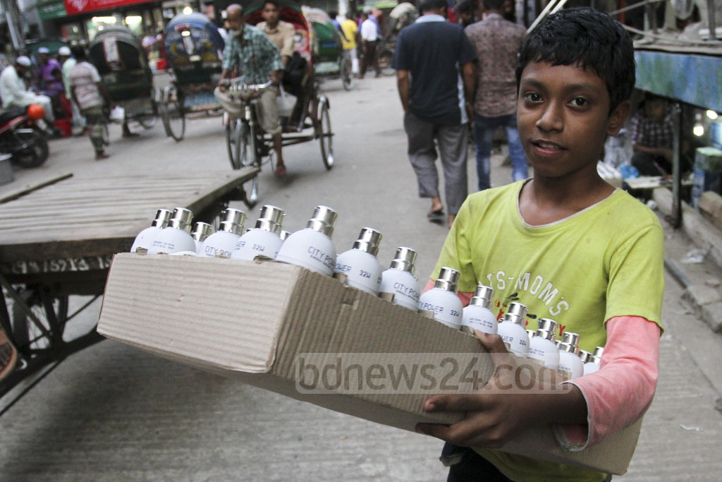 A child carrying a carton of energy-saving lights at Patuatuli in Old Dhaka on Thursday. The bulbs made from parts imported from China are sold for Tk 70-120 apiece. Photo: Asif Mahmud Ove