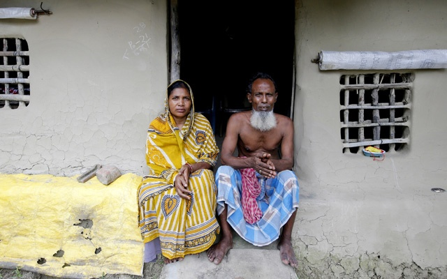 Sheikh Aftab Uddin, 66, and his wife Mamta Bibi, 50, pose for a picture outside their new mud house after their previous house was washed away due to high tides on Ghoramara Island, India, Aug 19, 2018. REUTERS