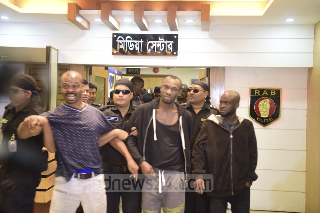 Fourteen nationals of different African countries, arrested for using the social media to deceive people, are brought to the RAB media centre at Dhaka's Karwan Bazar on Thursday.