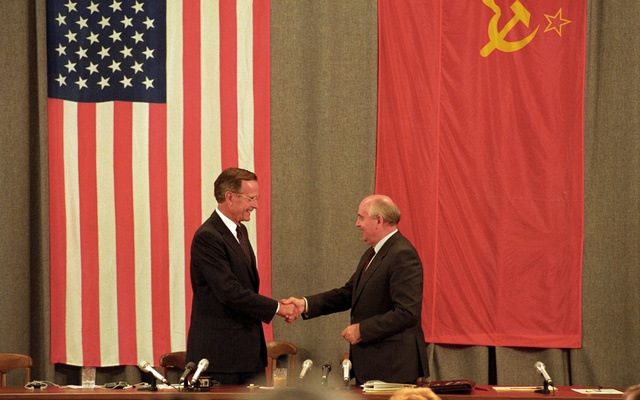 FILE PHOTO: US President George HW Bush (L) and Soviet President Mikhail Gorbachev shake hands in front of US\ and Soviet flags at the end of a news conference in Moscow July 31, 1991. REUTERS/Rick Wilking/File Photo