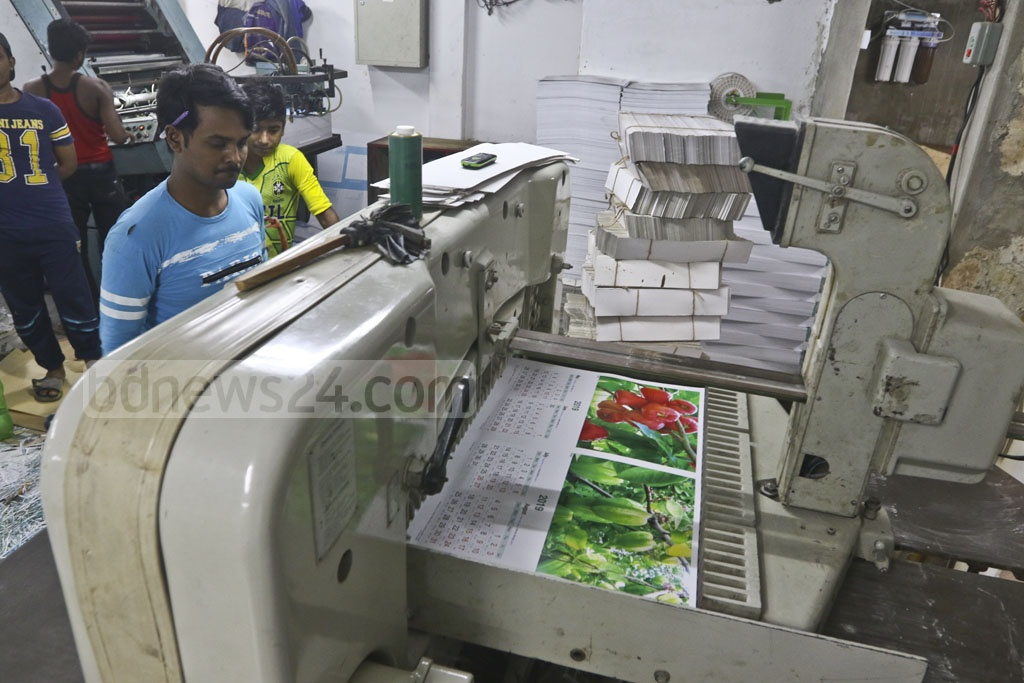 The demand for paper calendars is high ahead of the New Year. Workers pass busy hours printing calendars in Dhaka's Fakirapool on Tuesday. Photo: Abdullah Al Momin