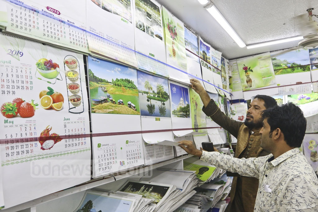 Workers put calendars up for sale at a shop in the capital's Purana Paltan area on Tuesday. Photo: Abdullah Al Momin