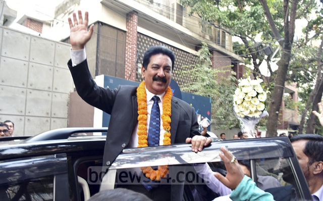 Jatiya Party's new Secretary General Mashiur Rahman Ranga waving at supporters after being greeted with flower as he arrived at the party's Banani offices in Dhaka on Monday.
