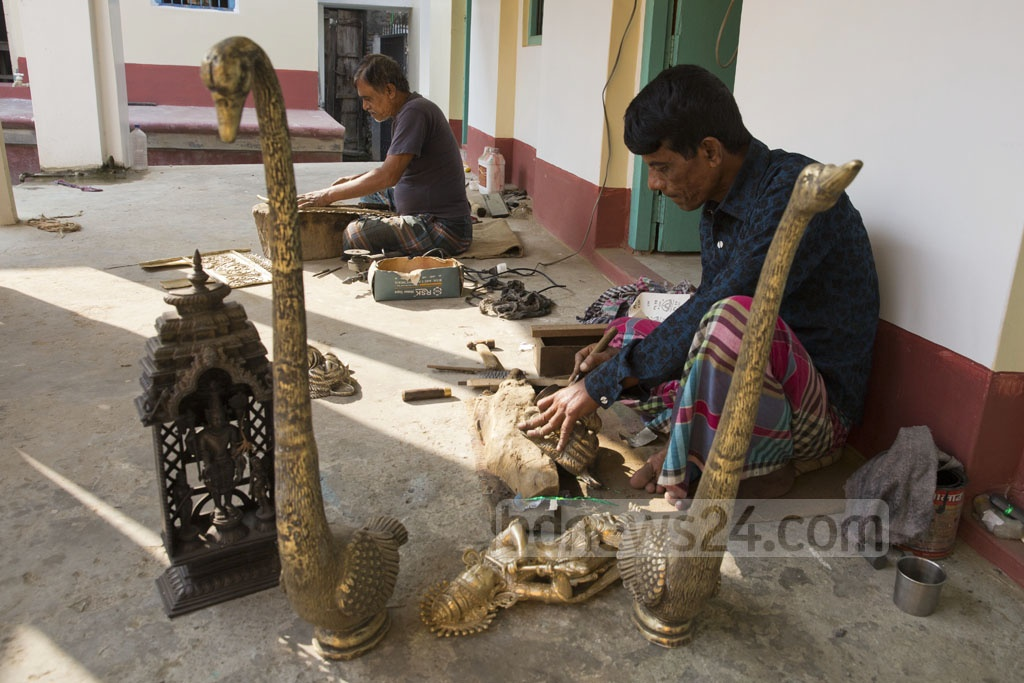 Sukanta Banik, one of the most prominent traders of metal crafts in Dhaka's Dhamrai, has kept the traditional business alive in his locality for a long time. Workers are seen at his house polishing sculptures on Wednesday. Photo: Mostafigur Rahman