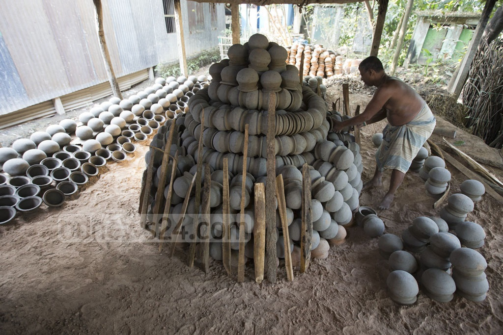 A potter readies a kiln for drying earthen pots at Shimulia Paal Para in Dhaka's Dhamrai on Wednesday. Photo: Mostafigur Rahman