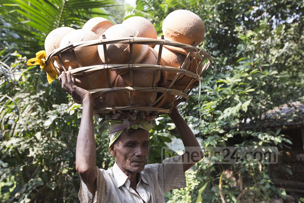 A potter carries earthen pots for sale at Shimulia Paal Para in Dhaka's Dhamrai on Wednesday. Photo: Mostafigur Rahman