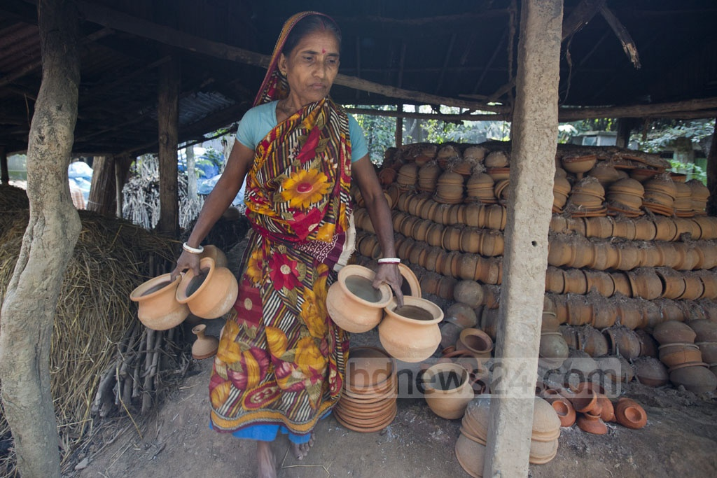 A potter removes earthen pots after drying on the kiln at Shimulia Paal Para in Dhamrai. Photo: Mostafigur Rahman