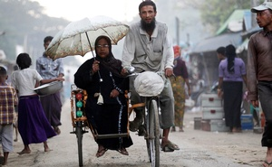 FILE PHOTO: People ride a tricycle at a internally displaced persons camp for Rohingya people outside Sittwe in the state of Rakhine, Myanmar Nov 15, 2016. REUTERS/Soe Zeya Tun/File Photo
