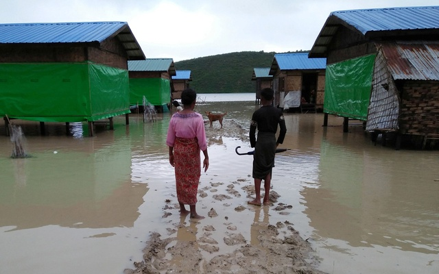 Muslim residents at Taungpaw an internally displaced people's camp walk through the flood to reach the new house built by the Myanmar government in central Rakhine, Myanmar, Jun 14, 2018. REUTERS/ Stringer