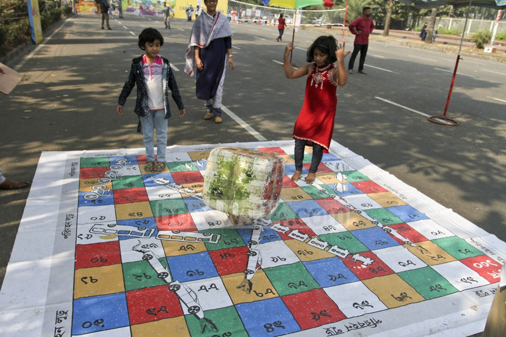 Two children play snakes and ladders on Manik Mia Avenue. Photo: Asif Mahmud Ove