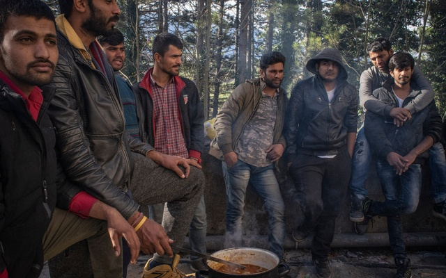 Migrants in Bihac, Bosnia, preparing lunch at a ruined orphanage that has been converted into a crude shelter. Thousands are trapped in the area. The New York Times