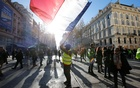 A protester wearing a yellow vest holds a French flag as he takes part in a demonstration of the