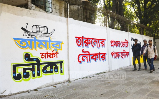 Defying a ban on graffitis for election campaign, writings and pictures soliciting votes for the ruling Awami League have been daubed across walls on the Dhaka University campus. Photo: Abdullah Al Momin