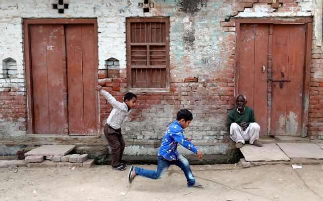 Children play as a man sits outside a house in Nayabans village in Bulandshahr district, Uttar Pradesh, India Dec 5, 2018. REUTERS