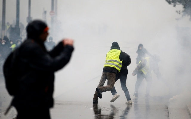 A man wearing a yellow vest tackles a protester as tear gas floats in the air during clashes with police at a demonstration by the