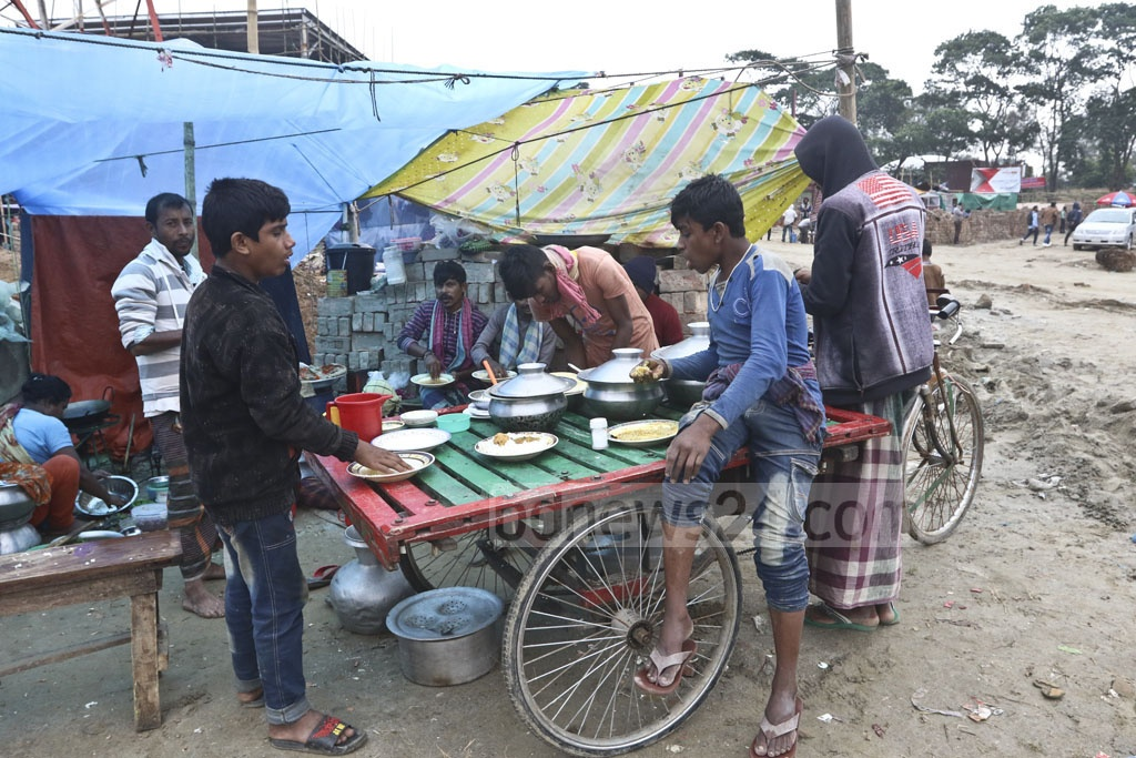 Workers eat at a temporary food stall on the site of the 28th Dhaka International Trade Fair in Sher-e-Bangla Nagar. Photo: Abdullah Al Momin