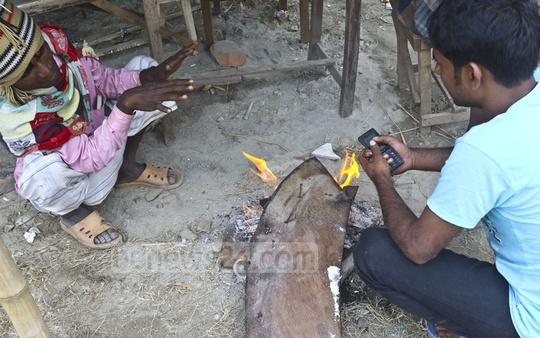 Labourers gather around a fire for warmth in Dhaka's Sher-e-Bangla Nagar area as cyclone Phethai brings rain and cloudy weather to the capital. Photo: Abdullah Al Momin