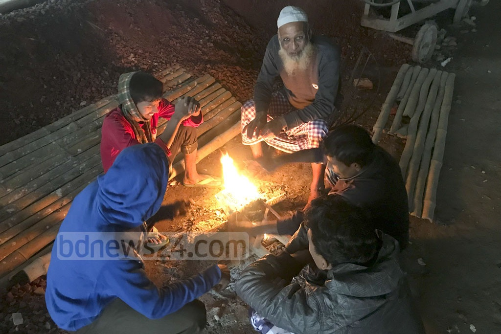 Construction workers warm themselves up by a fire in the Rampura area of Dhaka on Wednesday as the winter cold descends on the capital. Photo: Mostafigur Rahman