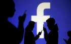 FILE PHOTO: Silhouettes of mobile users are seen next to a screen projection of Facebook logo in this picture illustration taken Mar 28, 2018. REUTERS