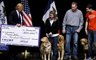 FILE PHOTO: US Republican presidential candidate Donald Trump presents a mock check from the Trump Foundationre presenting $100,000 to members of the Puppy Jake Foundation, which provides military veterans with train