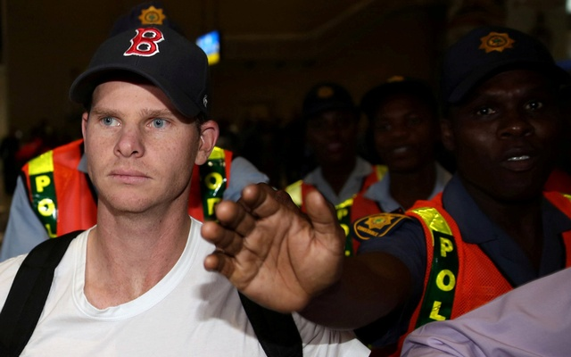 FILE PHOTO: Axed Australian cricket captain Steve Smith is escorted by Police officers as he departs at the O.R. Tambo International Airport in Johannesburg, South Africa March 28, 2018. Reuters