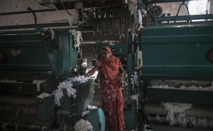 Manjula Popat clears cotton from processing machines at the Radhe Industries cotton-ginning factory in Kadi in the Indian state of Gujarat, Nov. 23, 2018. As the Federal Reserve raises rates, global investors are pulling their money out of emerging markets, damaging the world's most vulnerable economies. (Rebecca Conway/The New York Times)