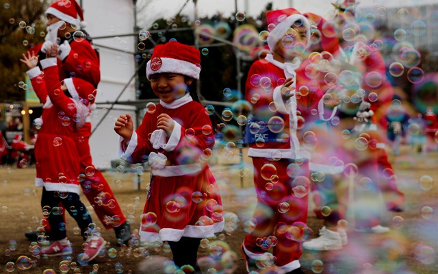 Children dressed as Santa Claus chase bubbles at a charity event